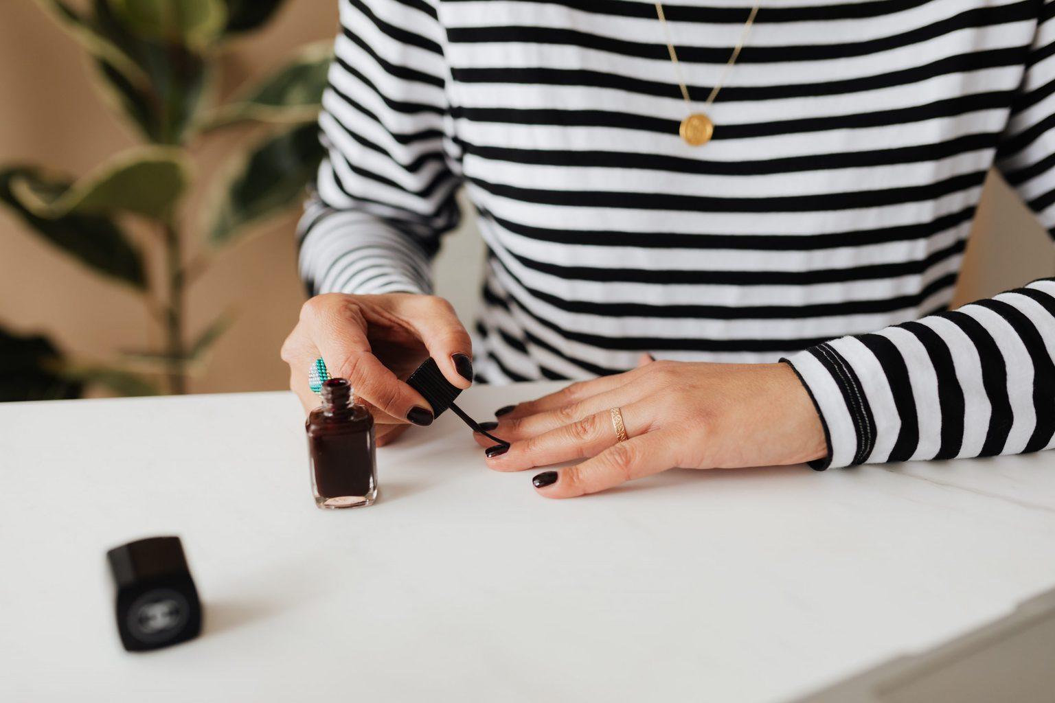 woman in striped shirt puts on black nail polish for an at home manicure from Karolina Grabowska at Pexels