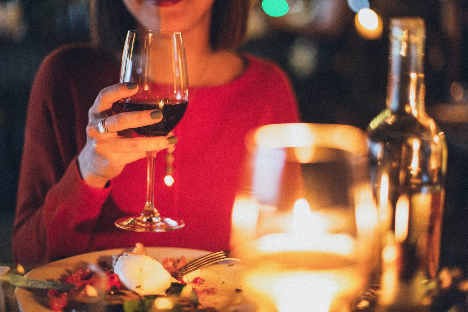 at home date ideas woman holding glass of wine over dinner table source: elinasazonova from Pexels