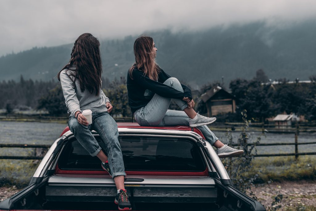 Stock photo of two girls are sitting by the car on a mountains background.