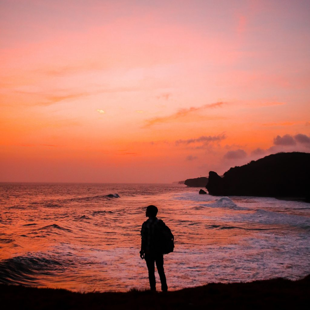 Stock photo of a man standing in front of a sunrise