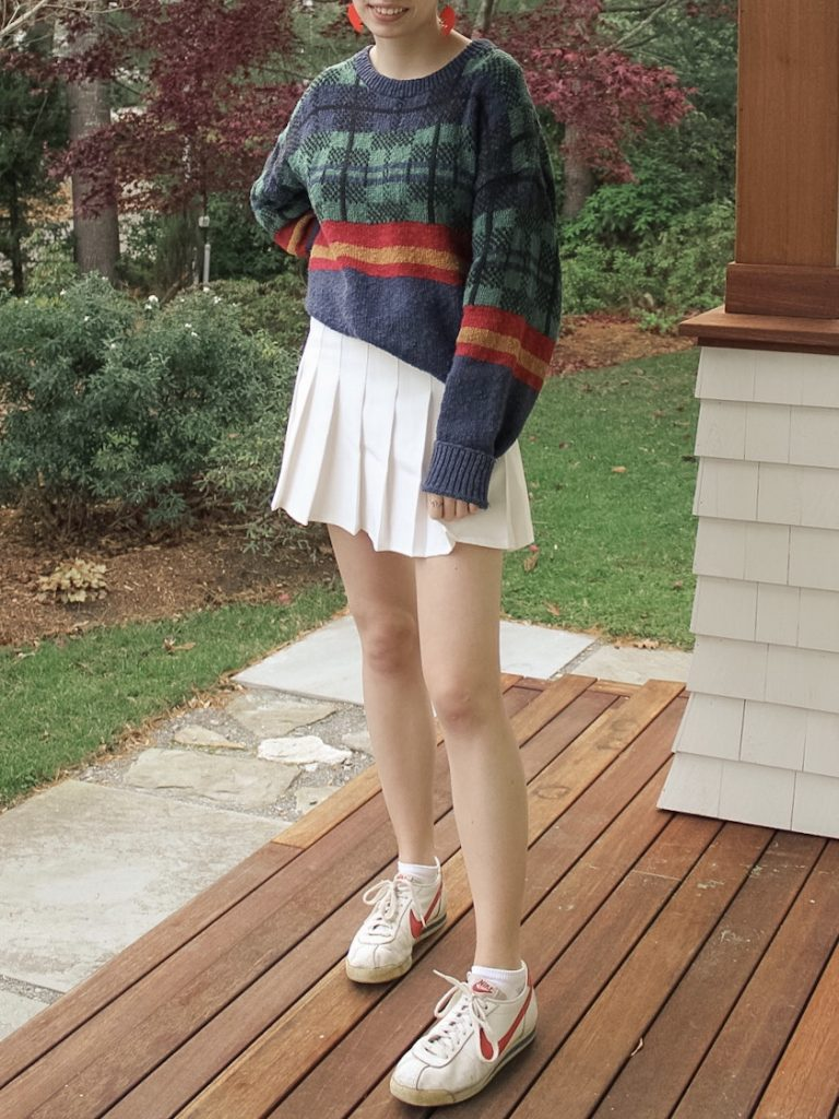 Photo of the author's outfit with a patterned sweater and a white tennis skirt