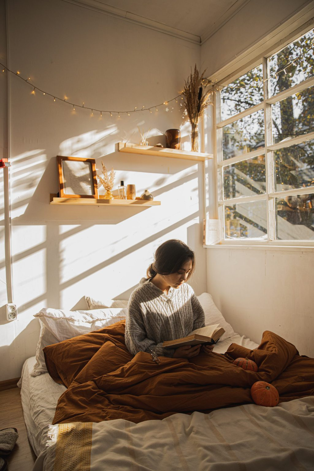 girl reading with book on bed