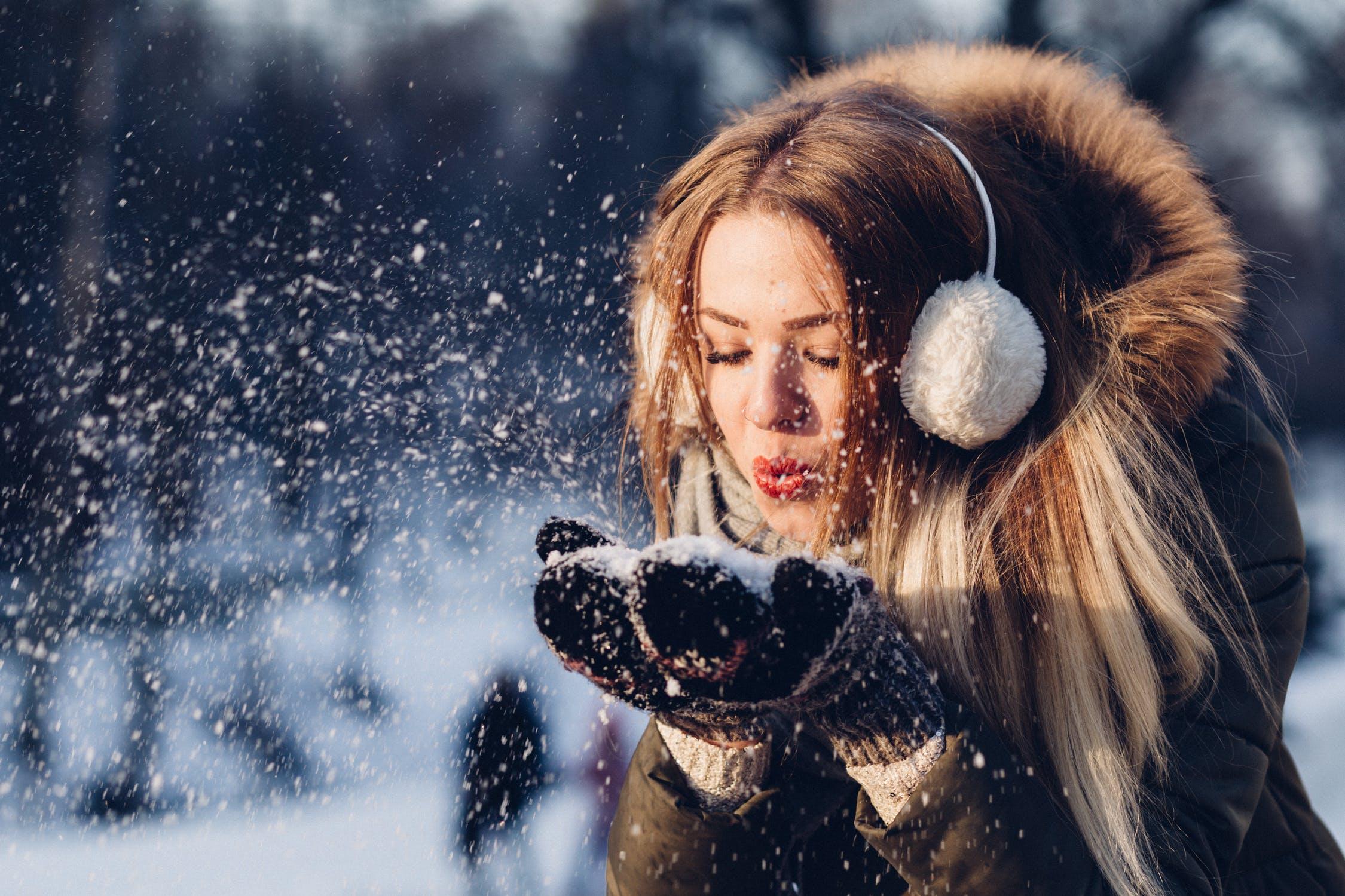 Woman blowing snow wearing earmuffs and a fur hood.