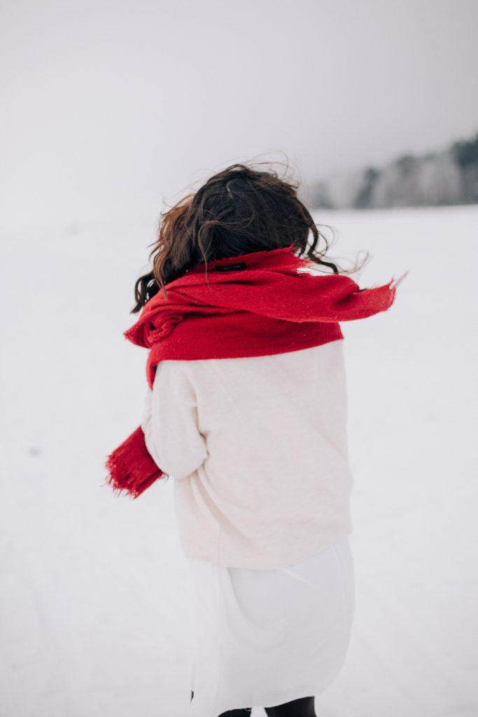 Woman wearing white in the snow with a red scarf, holiday style tips