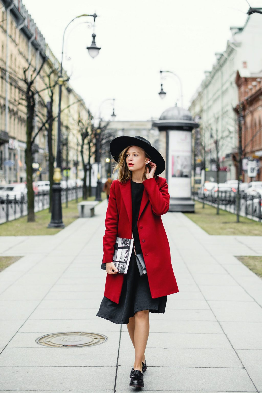 girl walking in all black outfit and red coat, holiday style tips
