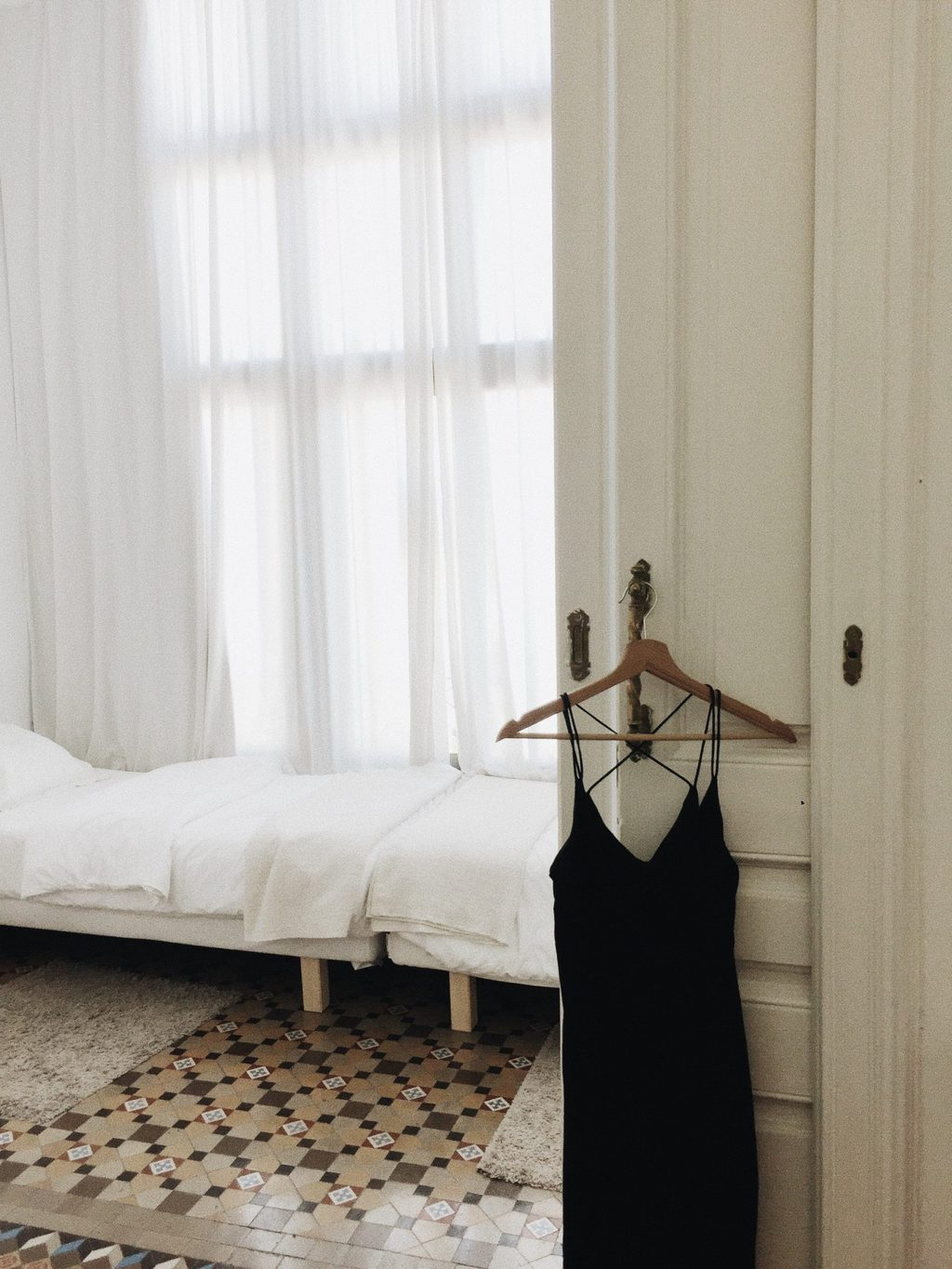 Little Black Dress hanging on a hanger on a door with a white bed in the background