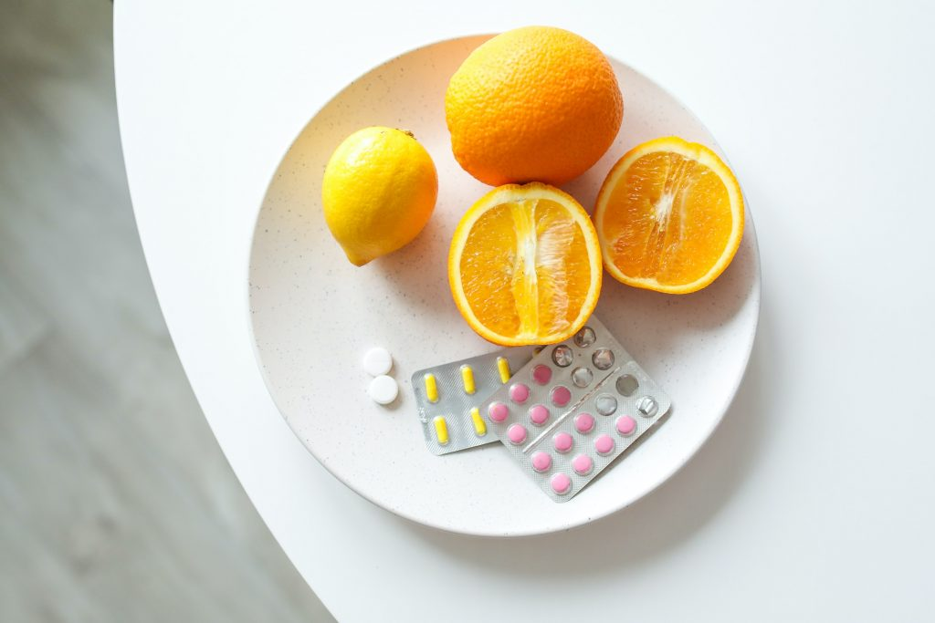 Best skin care habits - taking supplements. Stock photo of vitamins and oranges