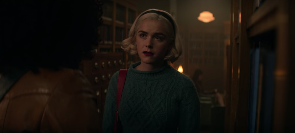 Screenshot from episode 1 of The Chilling Adventures of Sabrina Spellman, Season 4 - Sabrina in a green sweater and headband inside a library