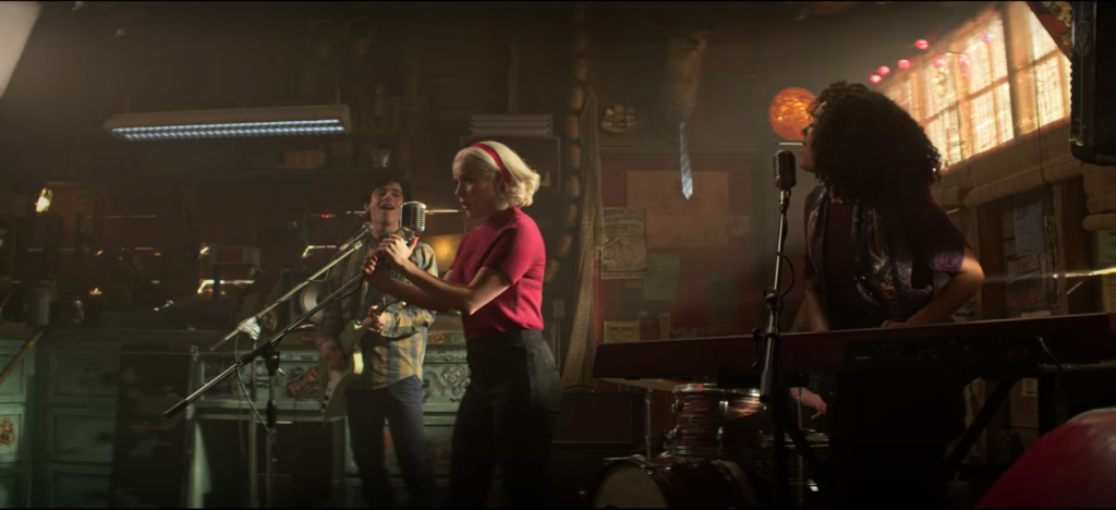 Screenshot from episode 5 of The Chilling Adventures of Sabrina Spellman, Season 4 - Sabrina performing in a garage in a red sweater and matching headband
