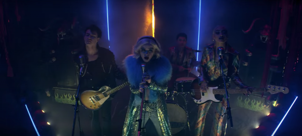 Screenshot from episode 16of The Chilling Adventures of Sabrina Spellman, Season 4 - Sabrina performing in a music venue in fur and sequin pants