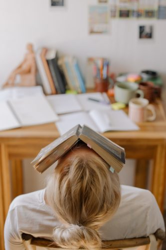 Photo of a person with a messy desk and a book on their head, college organization tips.