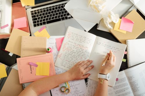 Messy desk with laptop, planners, notebooks, and journals, by Cottonbro from Pexels