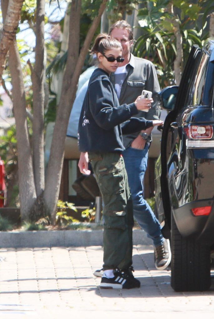 Kaia Gerber wearing a black hoodie, green army cargo pants, and black Addias sneakers