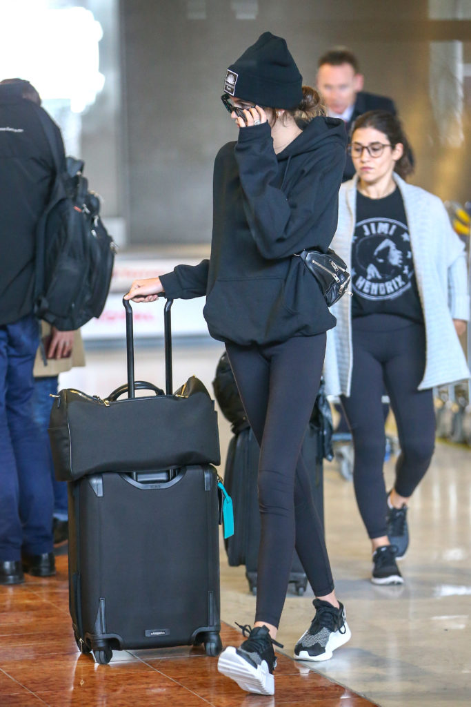 Kaia Gerber simple airport outfit with black leggings, black and white sneakers, oversized black hoodie, fanny pack and beanie