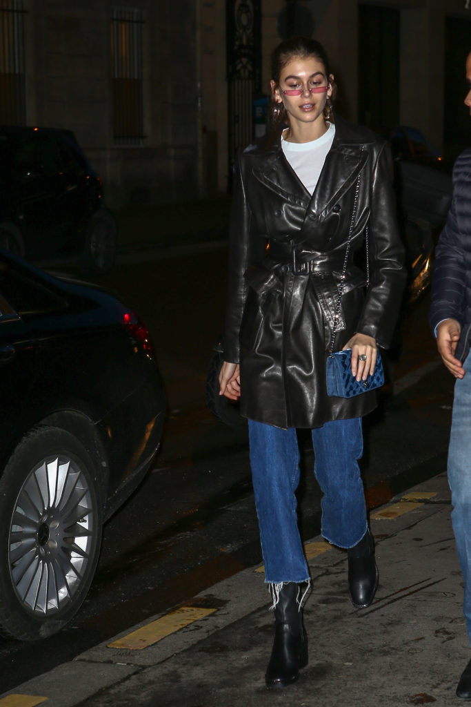 Kaia Gerber wearing a black vinyl trench coat and wide leg jeans with ankle boots and a crossbody bag