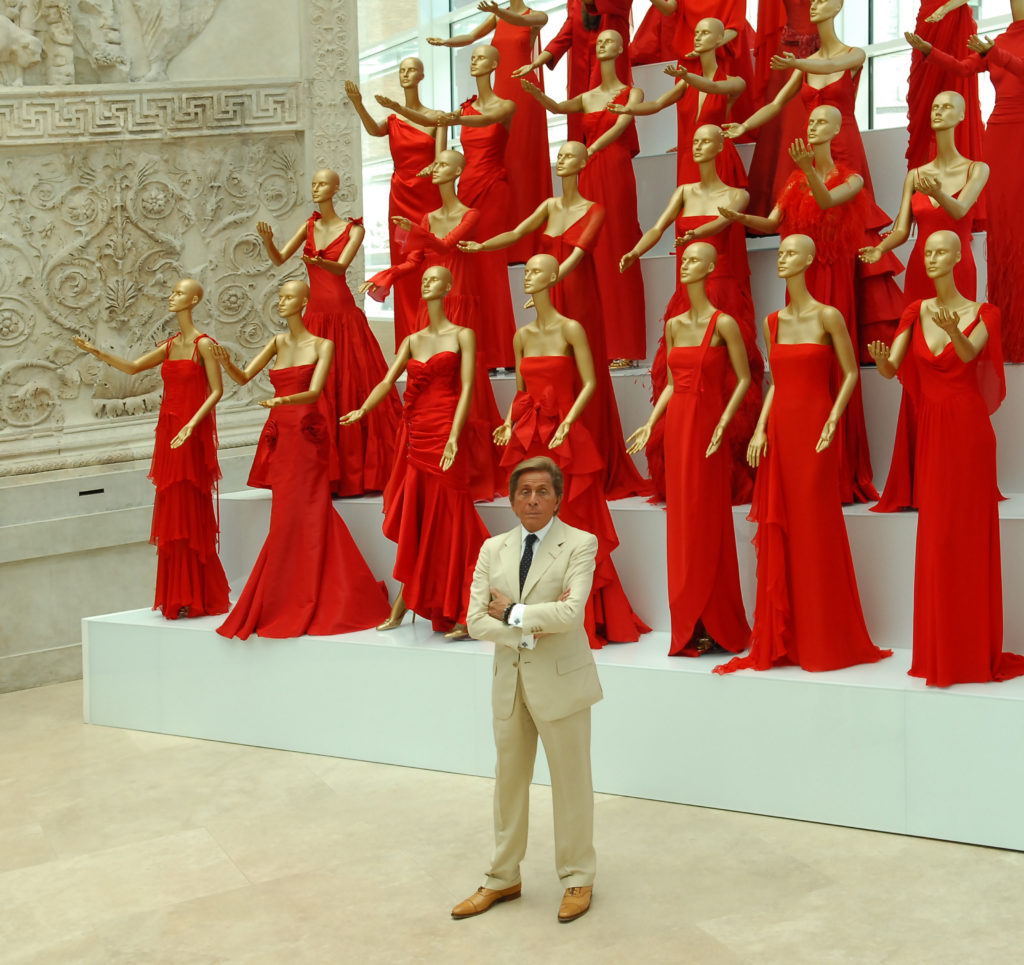 Valentino at an exhibit with his red dresses