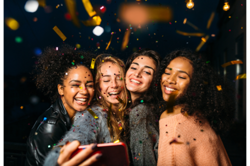 Photo of four girls celebrating a birthday while taking a selfie.