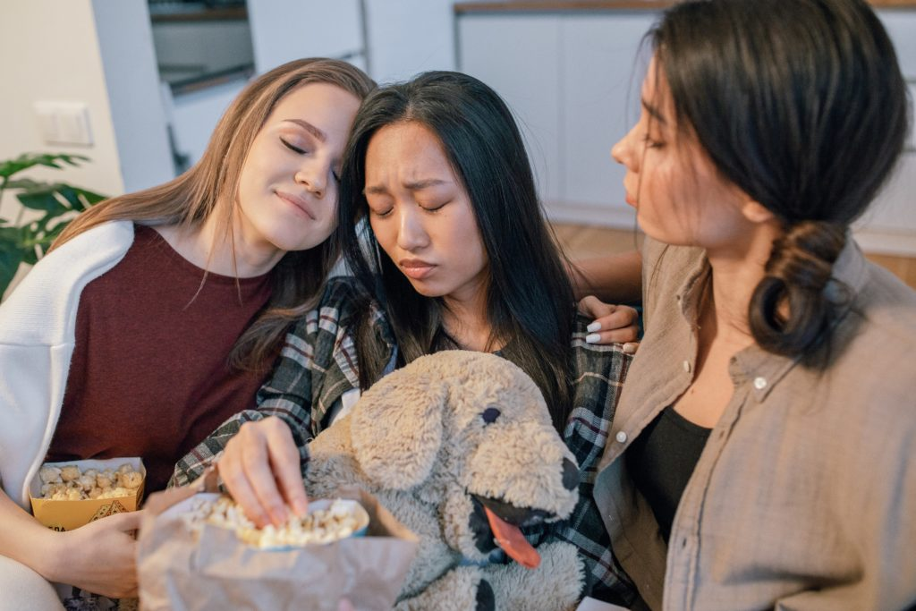 Three girls hugging with a dog toy.