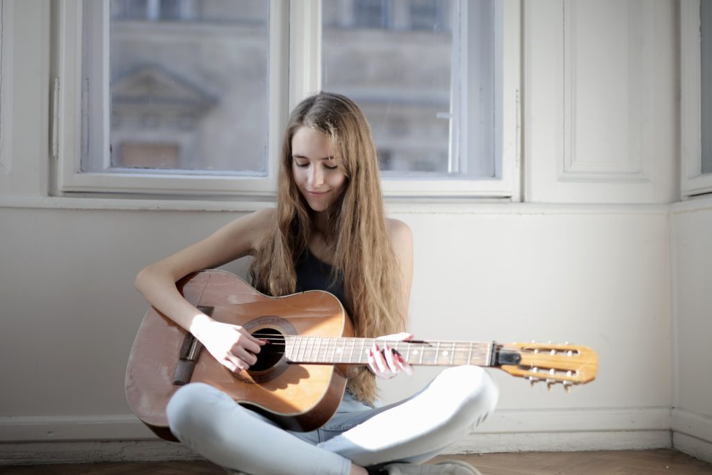 A girl sitting on the floor playing guitar.