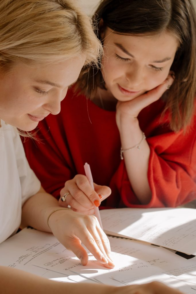 Two women looking at at some notes.