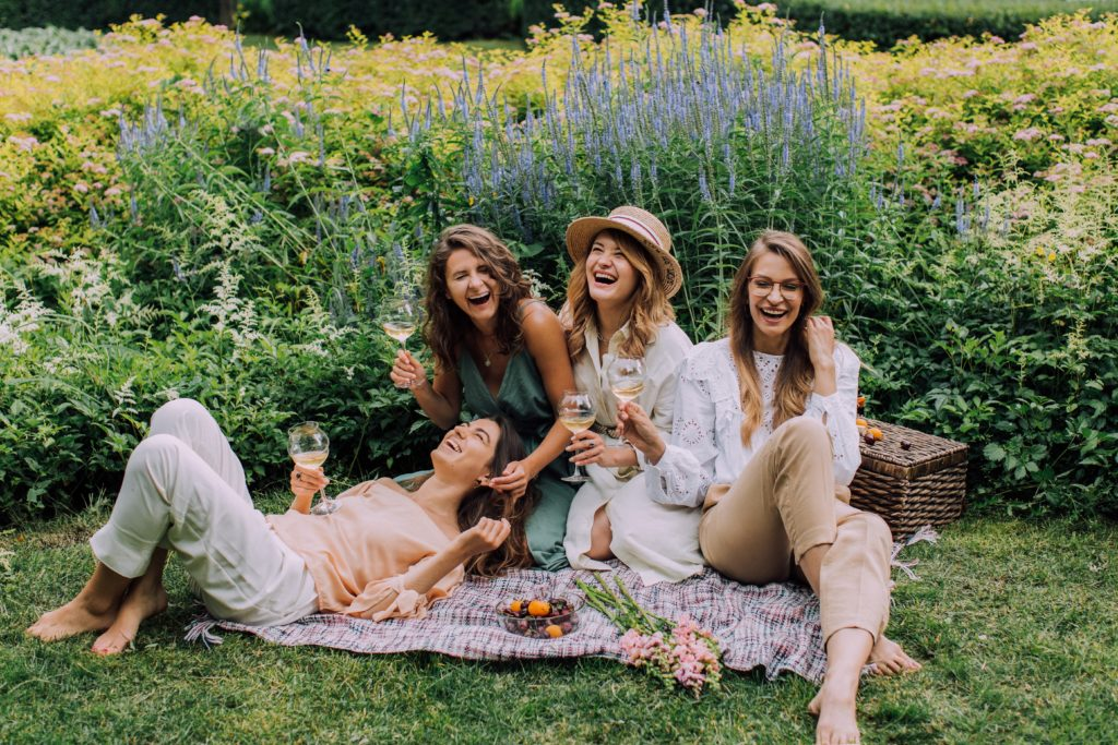 Friendship changes in college - Four girls having a picnic outside.