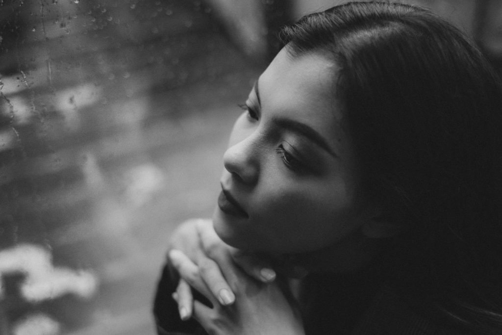 A black and white picture of a girl sitting by a rain covered window.
