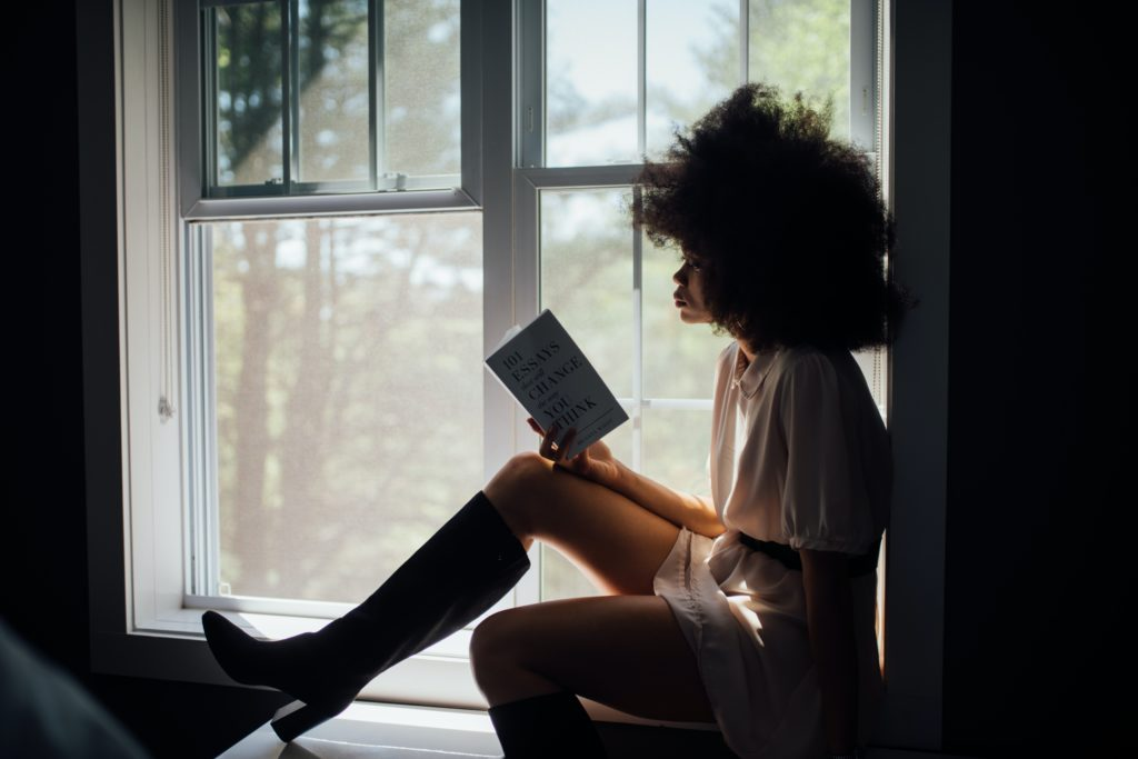 A girl sitting down by a window reading.