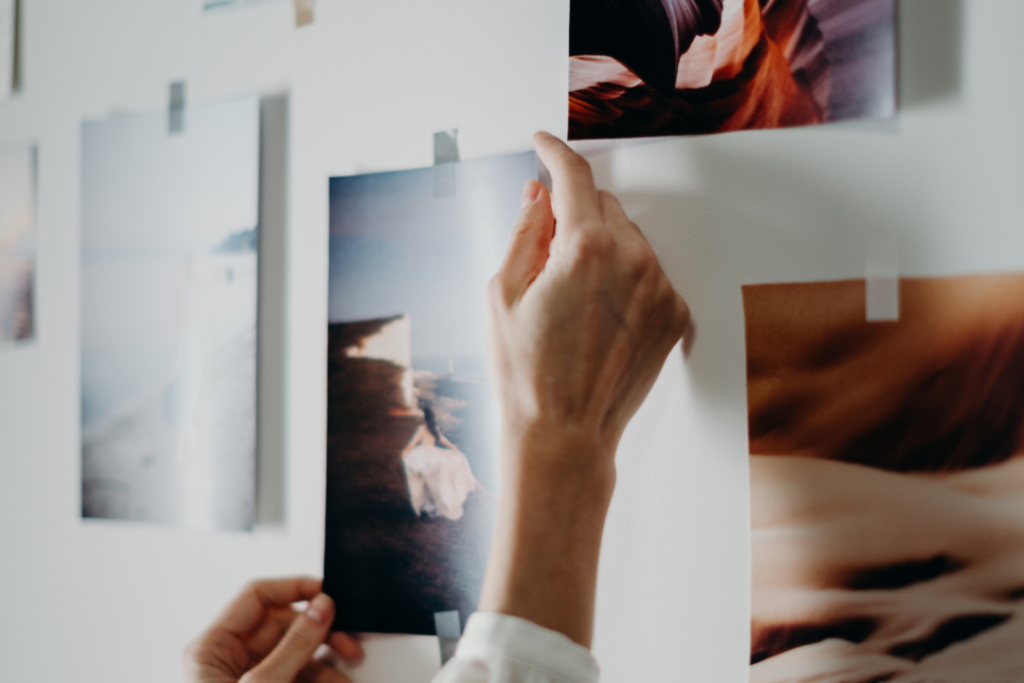 Woman taping photos to wall