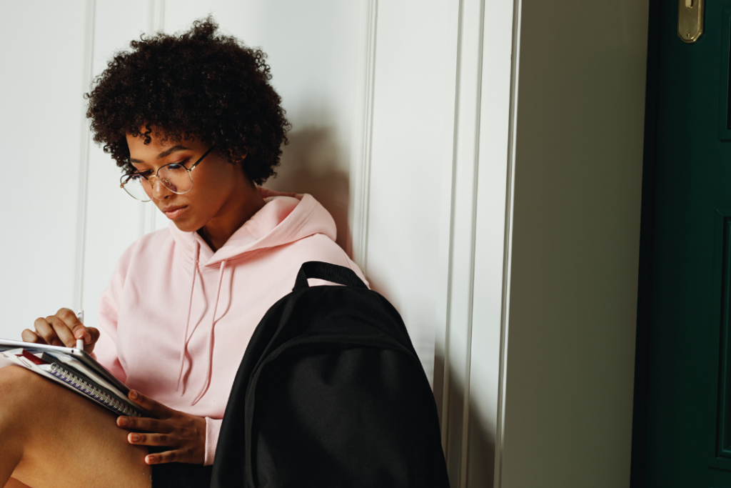 Woman wearing a pink sweatshirt studying for an exam