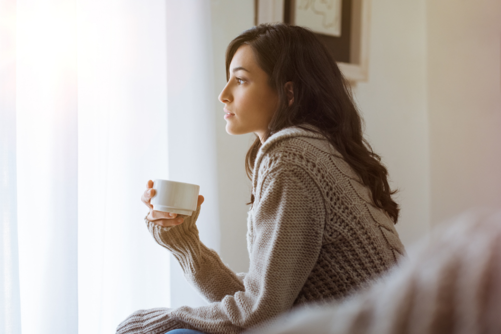 Woman thinking with coffee in hand