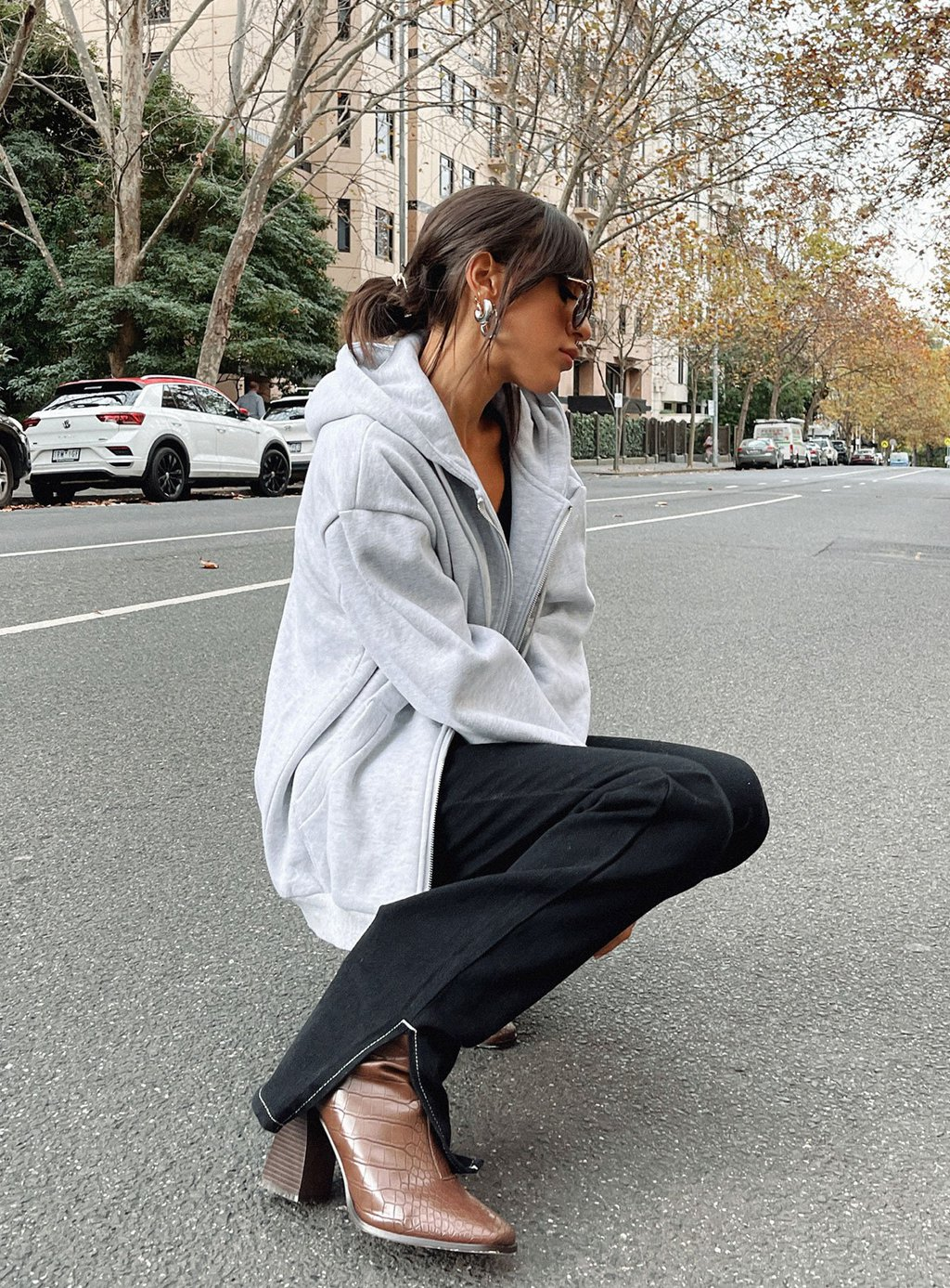 Photo from Princess Polly of a woman wearing fall wardrobe essentials including brown leather boots, flared pants, and a zip sweatshirt
