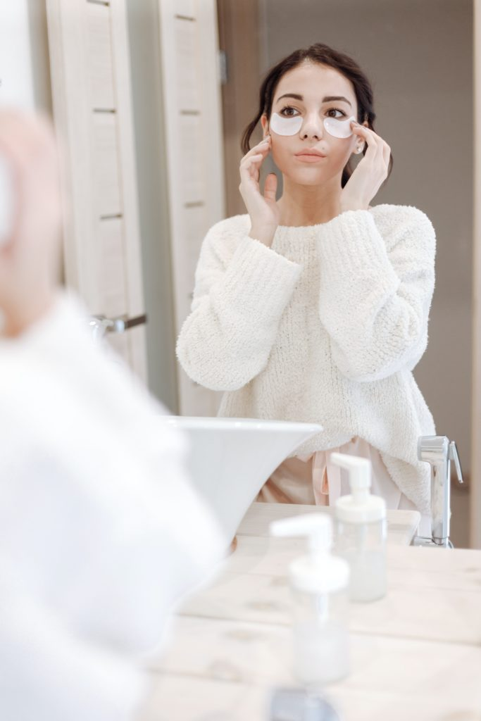 Woman with eye masks on looking in the mirror