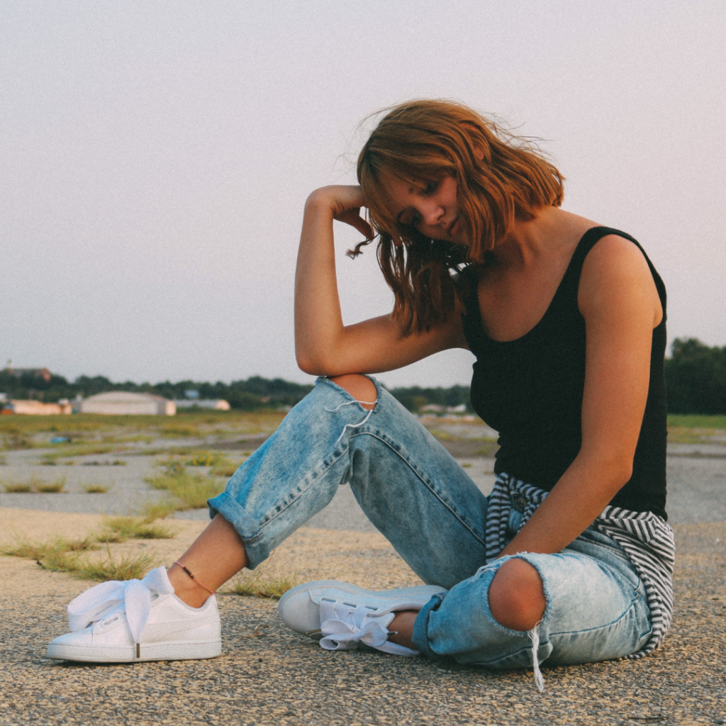 Woman wearing ripped jeans, white sneakers, and a white tank top while sitting on the ground in a parking lot