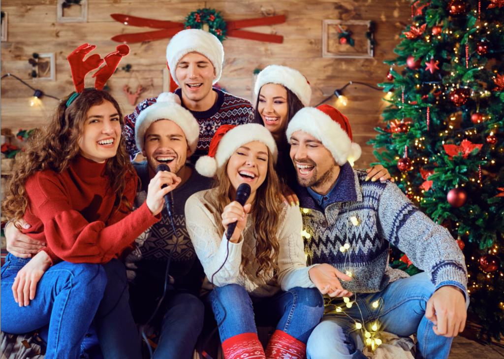 People singing karaoke while wearing santa hats in a festive scene - things to do over winter break