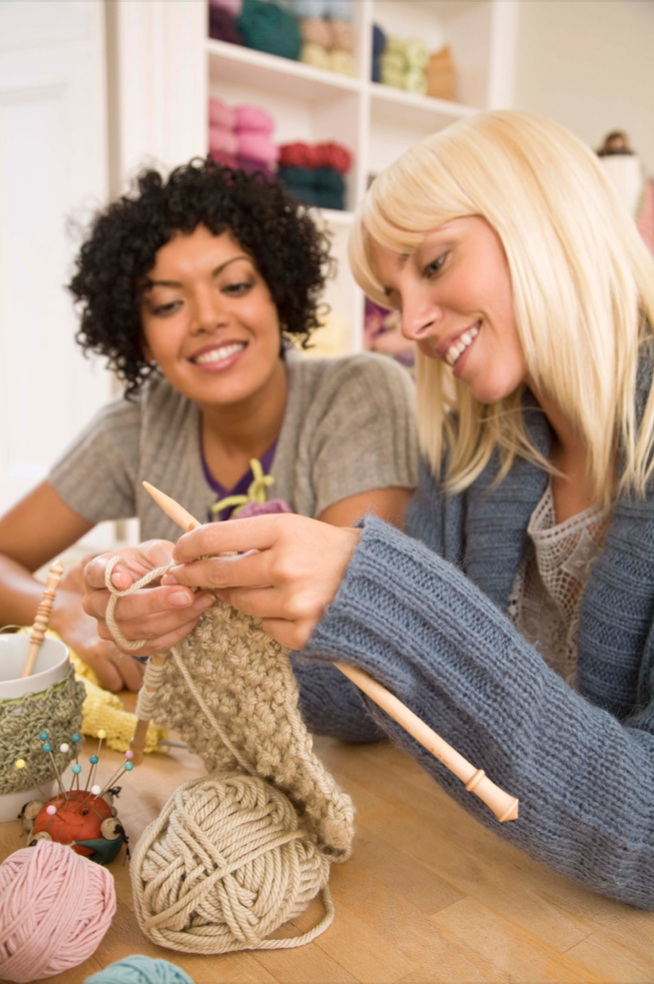Two women knitting scarves with tan yarn