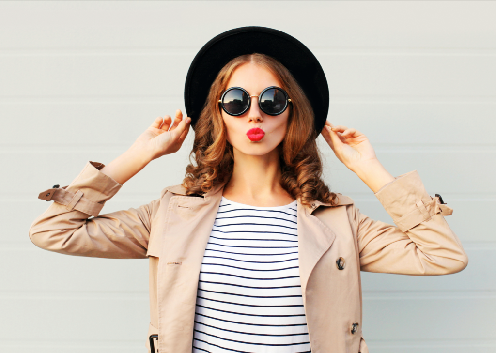 Woman wearing a black hat, trench coat, and white and black horizontal striped shirt with round sunglasses and pink lipstick - things to do over winter break