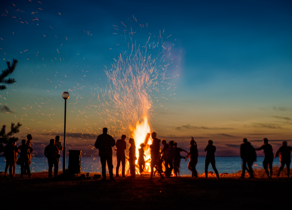 People standing around a bonfire - things to do over winter break