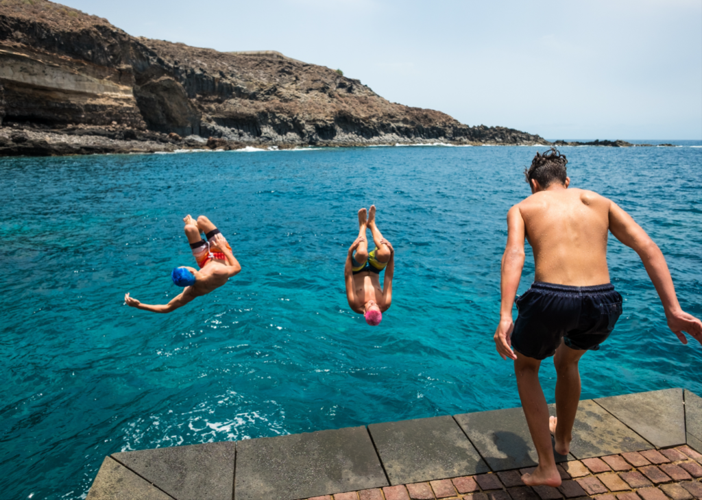 People doing backflips into the ocean - things to do over winter break