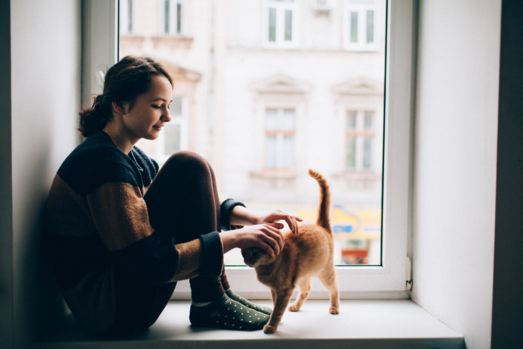 Photo of a woman pet sitting for a cat