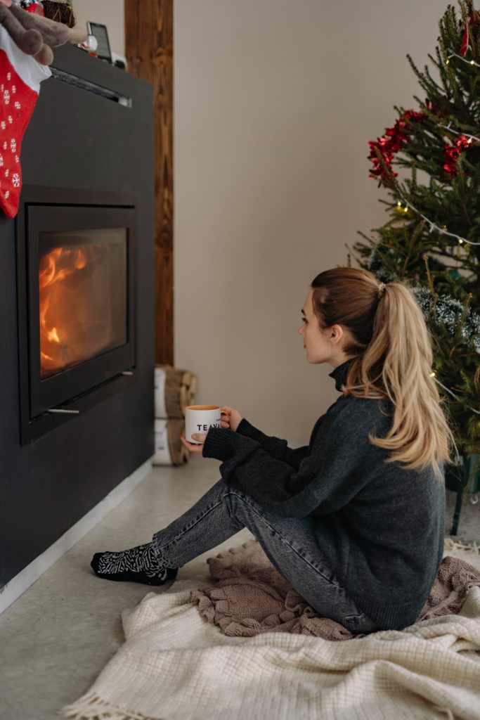 woman sitting in front of a fire drinking hot tea